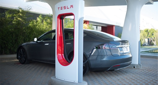 auto elektromobil Tesla Model S u nabíjecí stanice stojanu Tesla Supercharger