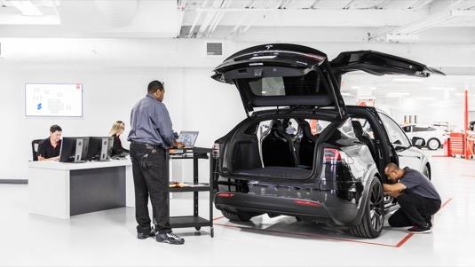 Oprava elektromobilu Tesla Model X v servisním centru automobilky. U téhle práce se nezašpiníte.
