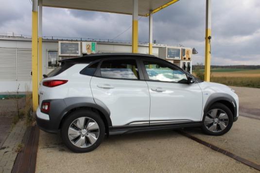 Elektromobil Hyundai Kona Electric v popředí, v pozadí chátrající čerpací stanice. Kdo se nepřizpůsobí nové době, dopadne podobně.