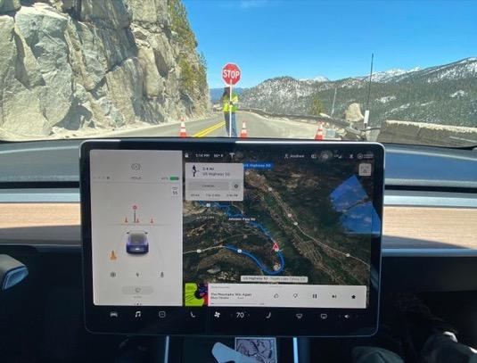 Tesla zastavuje před značkou Stop, kterou drží dělník na silnici