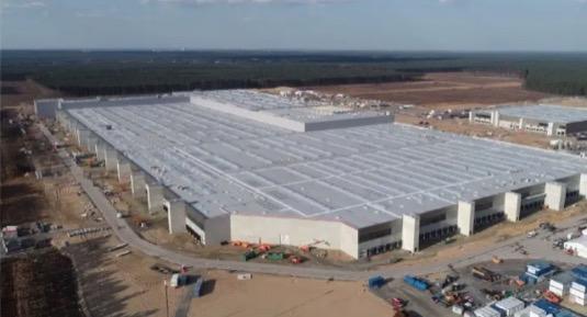 Aktuální fotka Gigafactory Berlín, kde se už letos začnou vyrábět elektromobily Tesla Model Y. Uvnitř už se zabydluje veškeré vybavení.